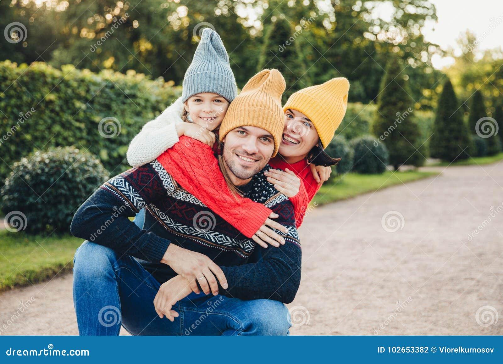 Красивый человек имеет хорошее отношение с женой и малая дочь которая обнимает его от задней части, имеет приятные улыбки Дружелю
