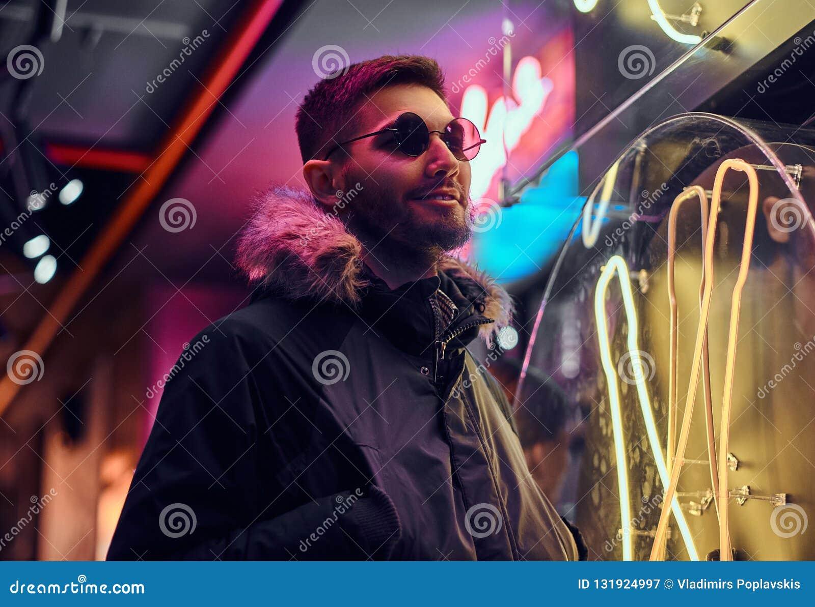 Красивый человек нося пальто и солнечные очки с руками в карманах, стоя в ночи на улице