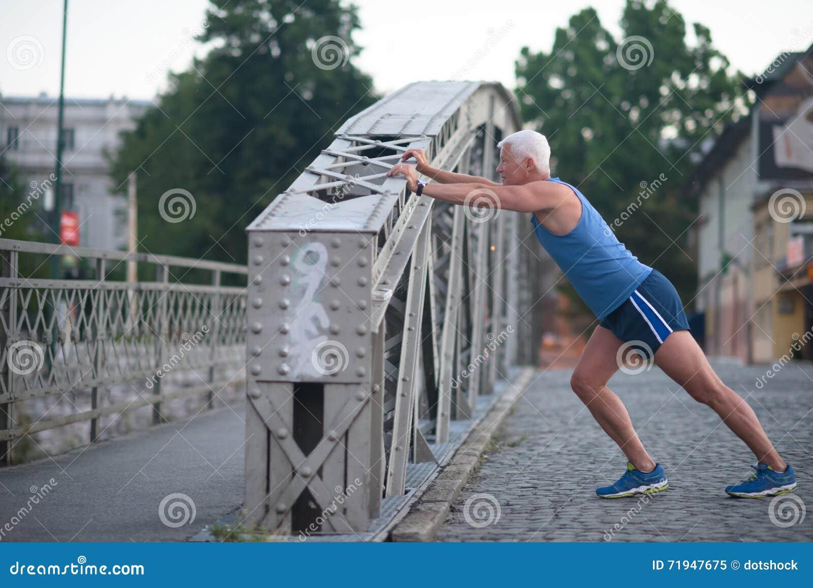 Красивый человек протягивая перед jogging