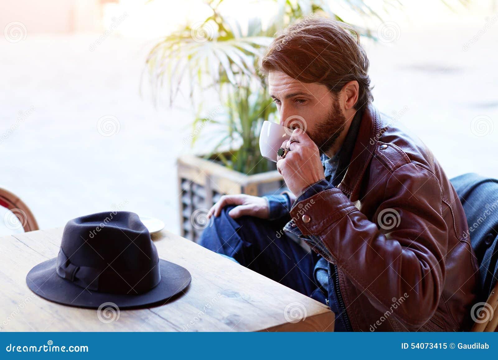Красивый человек сидя в ресторане и ждать друга который забыл его шляпу