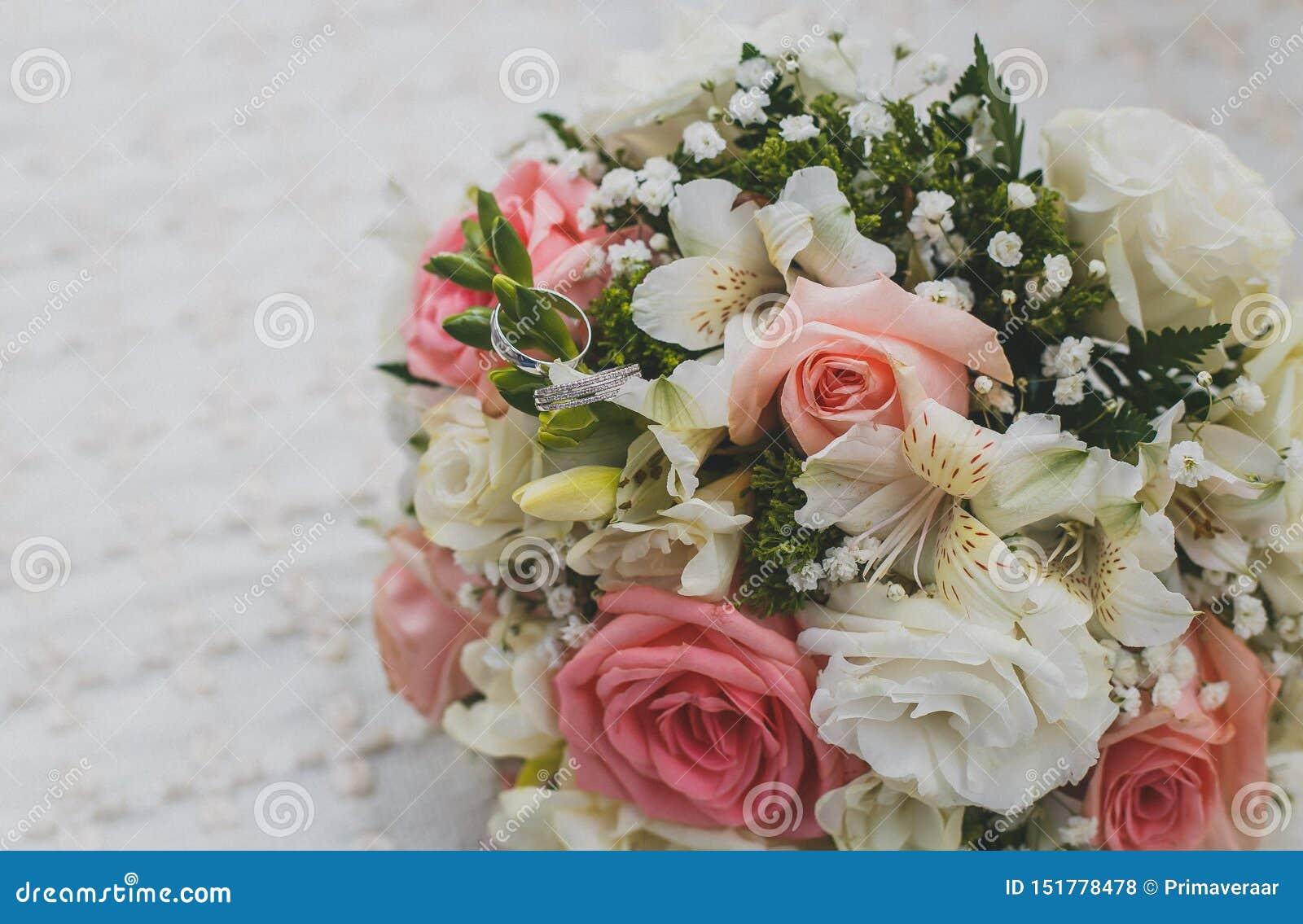 Красивый bridal букет, обручальные кольца белого золота на цветках