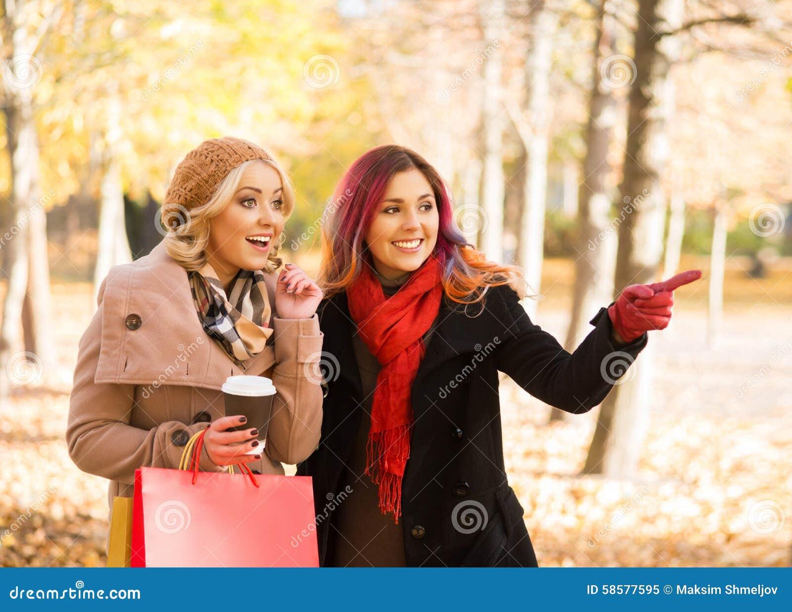 2 красивых женщины имея расслабляющий переговор с кофе