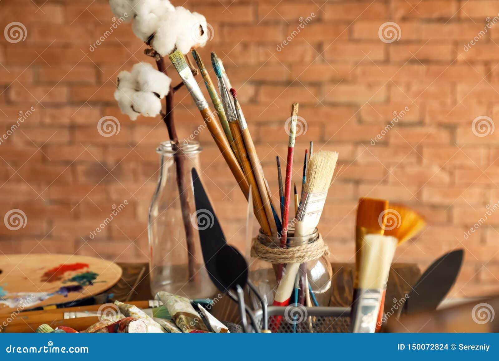 Краски и инструменты на деревянном столе в мастерской художника