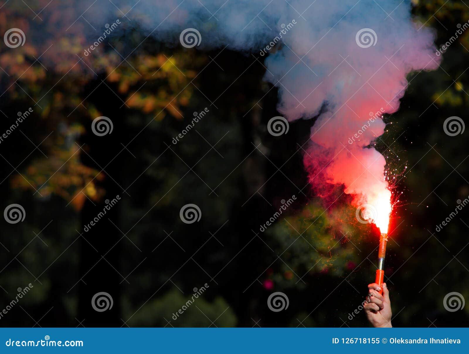 Красная бомба дыма в руке
