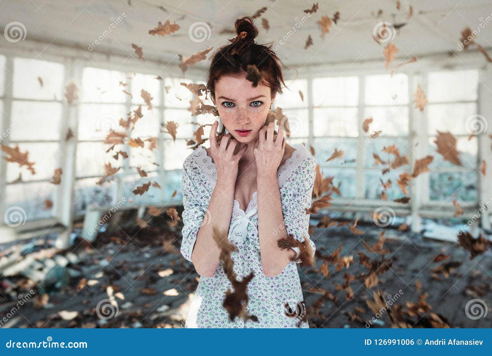 Красная девушка волос при веснушки стоя в падая листьях осени белизна осени изолированная принципиальной схемой