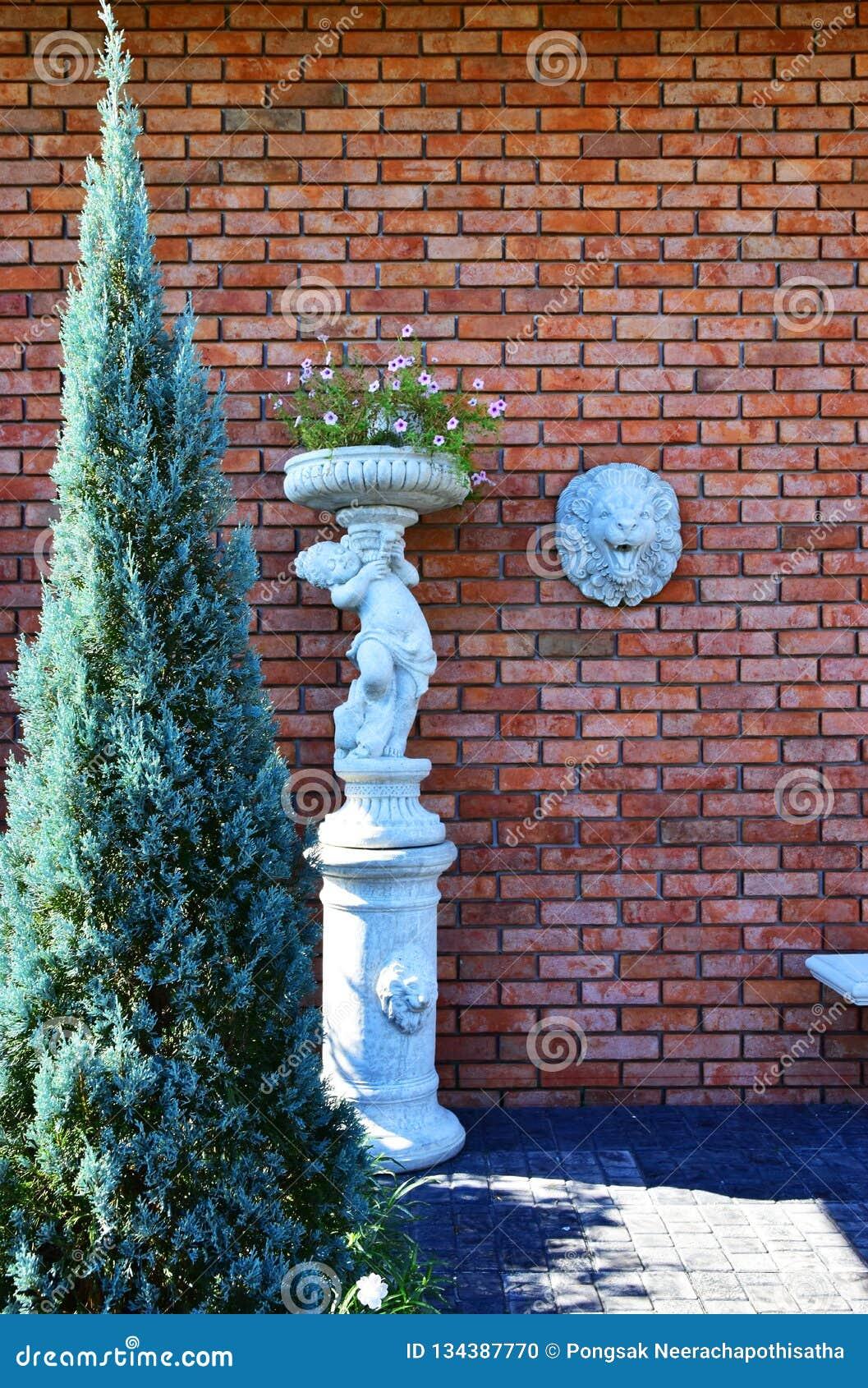 Красная кирпичная стена со скульптурой стороны льва