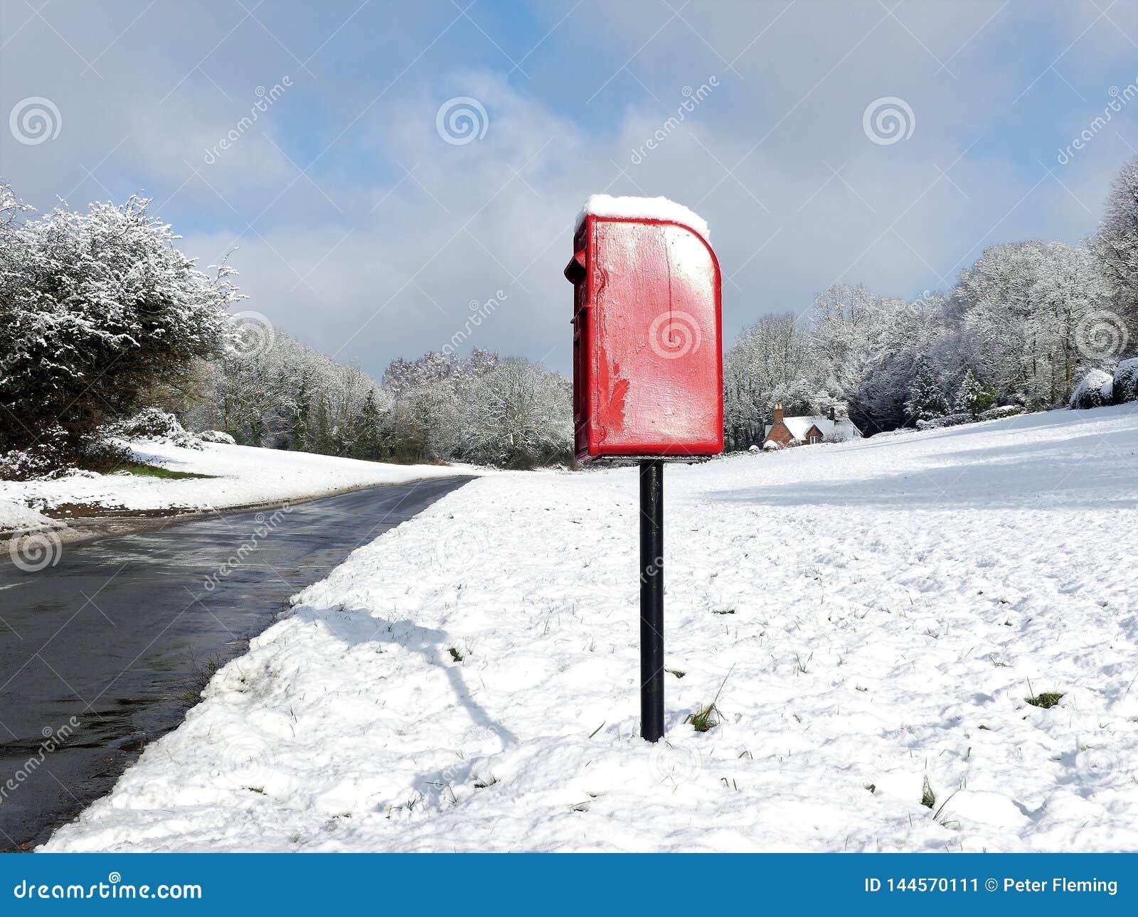 Красная коробка столба, майна конуры собаки, Chorleywood в снеге зимы