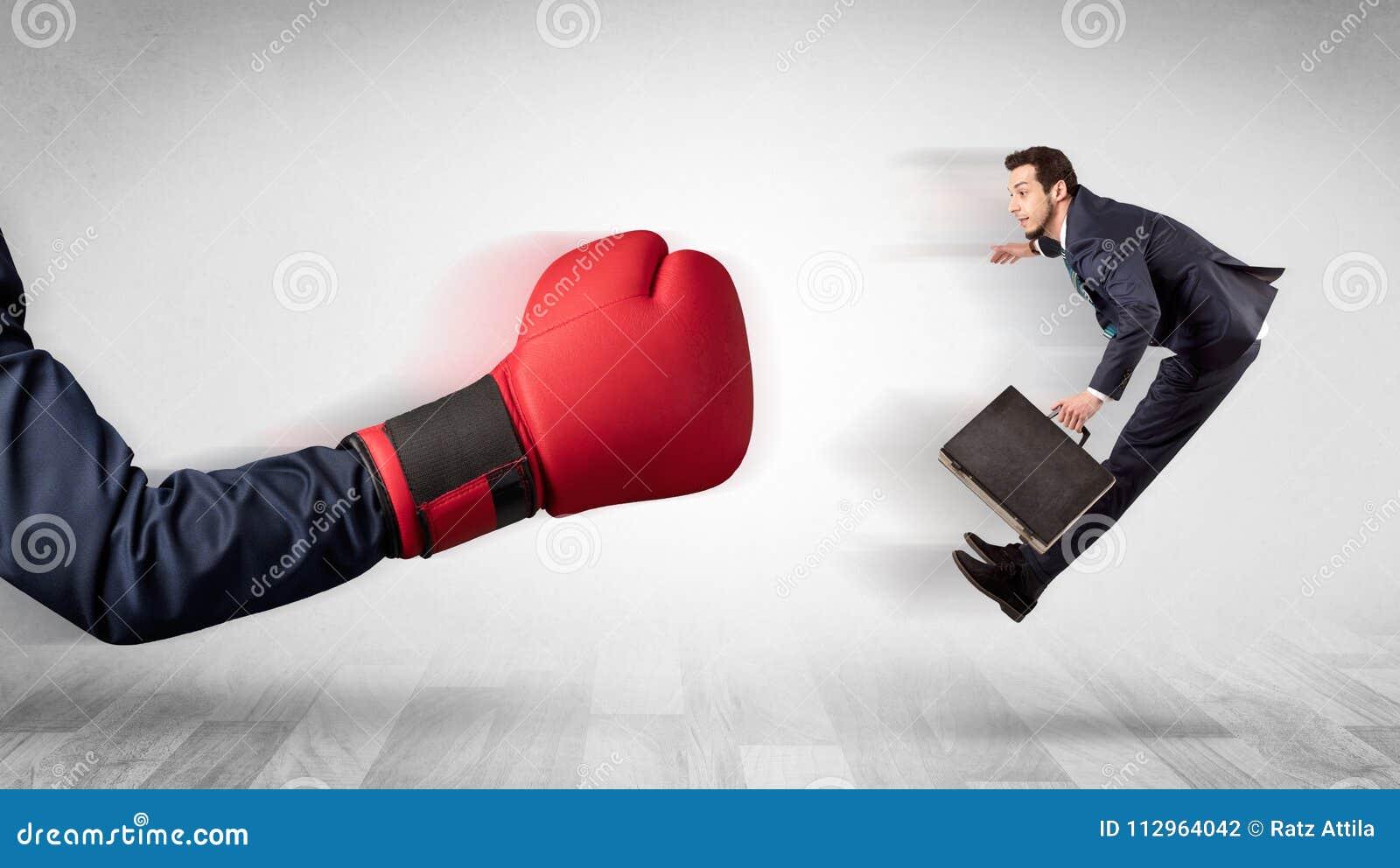 Красная перчатка бокса стучает вне маленьким бизнесменом