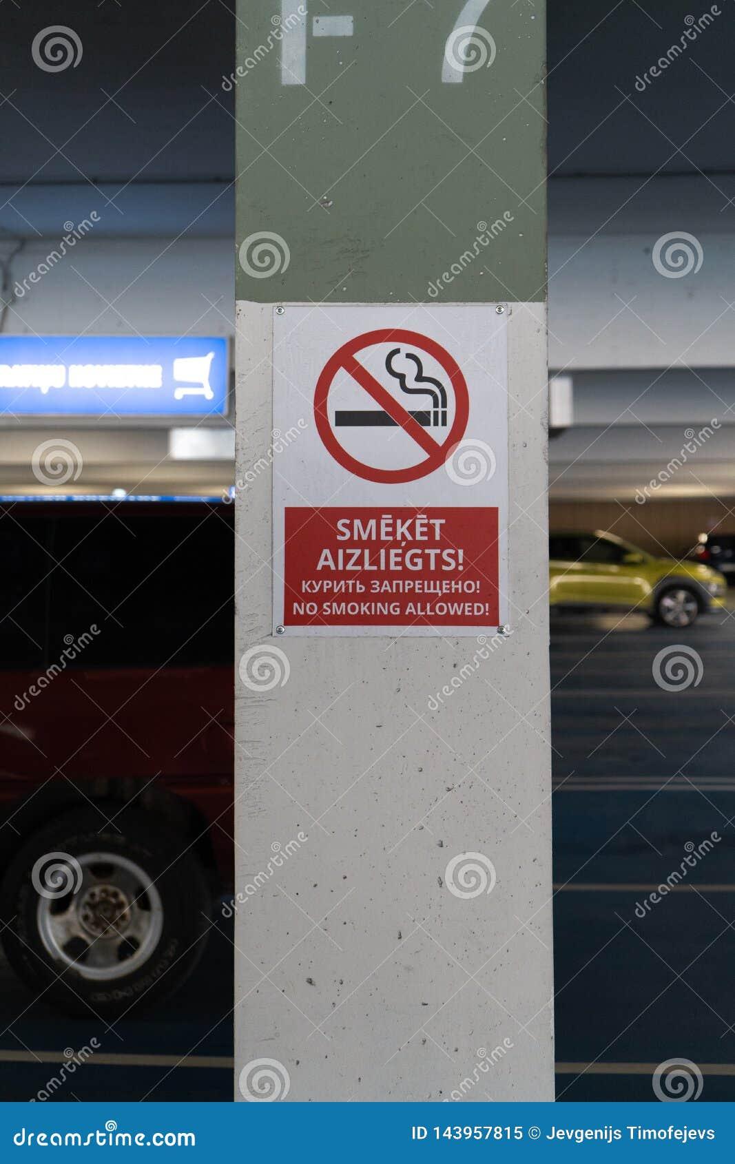 Красное для некурящих allower подписывает в 3 языках в подземной стоянке с автомобилями видимыми на заднем плане