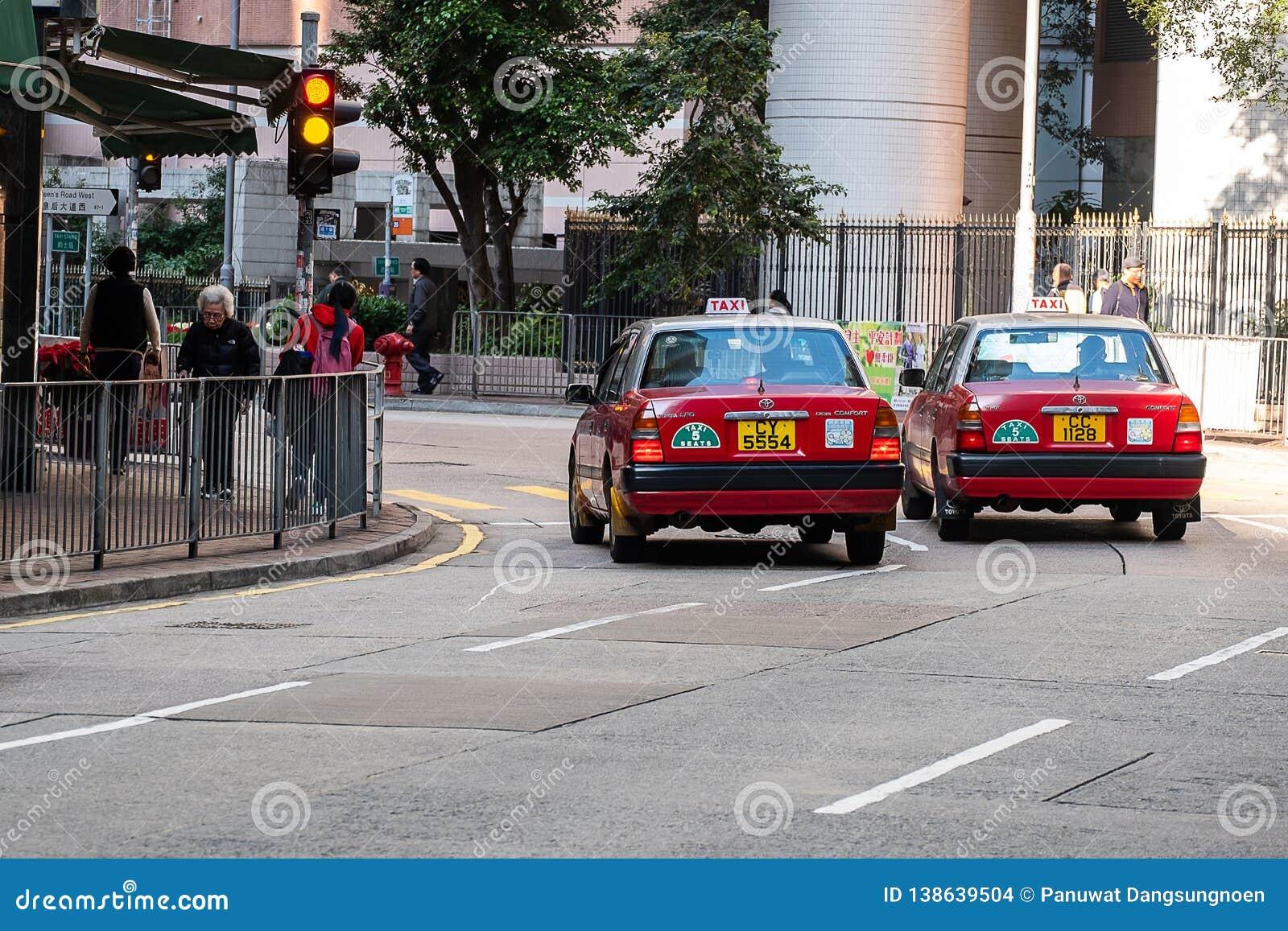 Красное и белое такси цветов, символ HK, на дороге Голливуд около района централи и Sheung болезненного; Гонконг, Китай, 16-ое де
