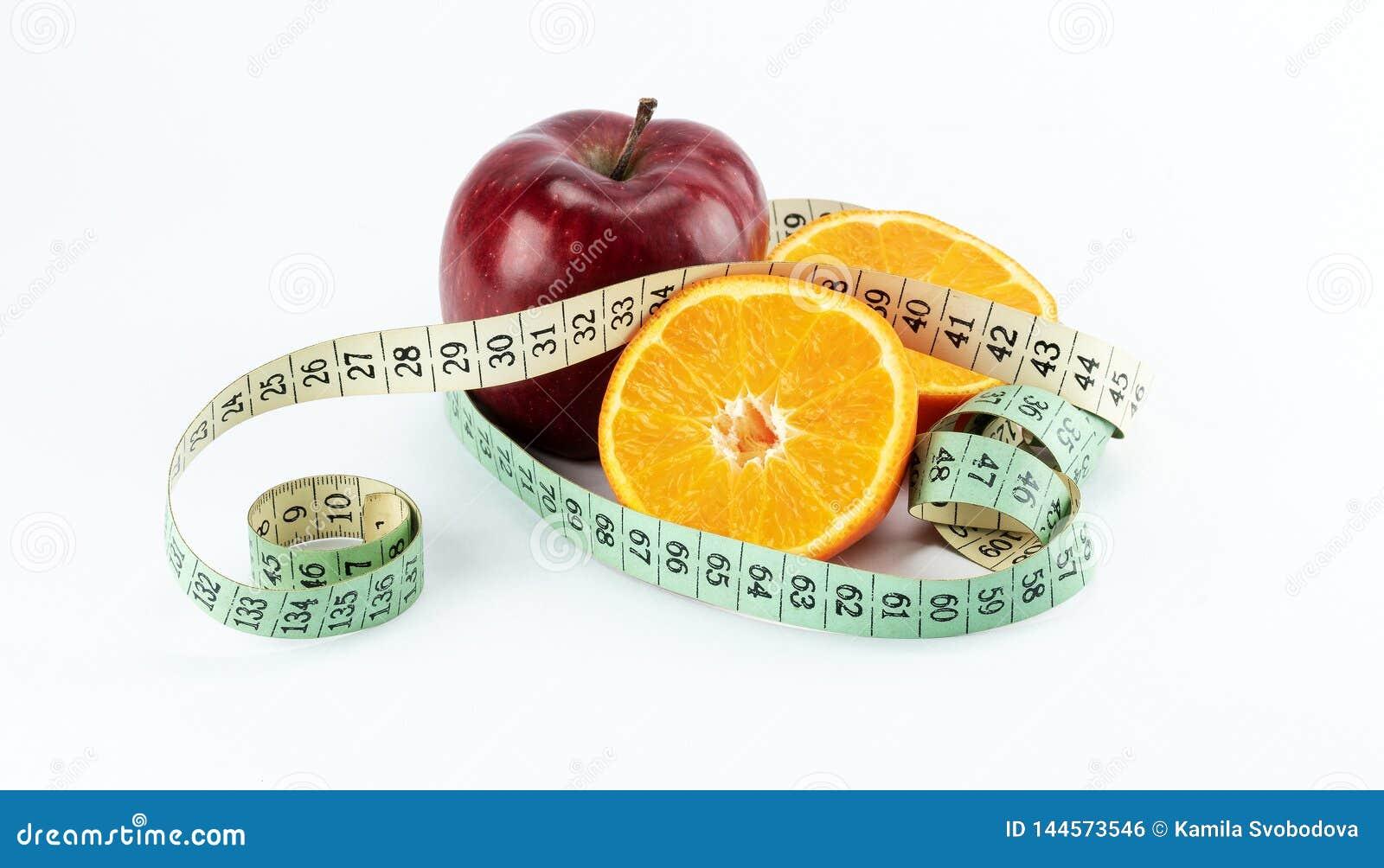 Красное яблоко с 2 половинами апельсинов в оболочке с измеряя лентой
