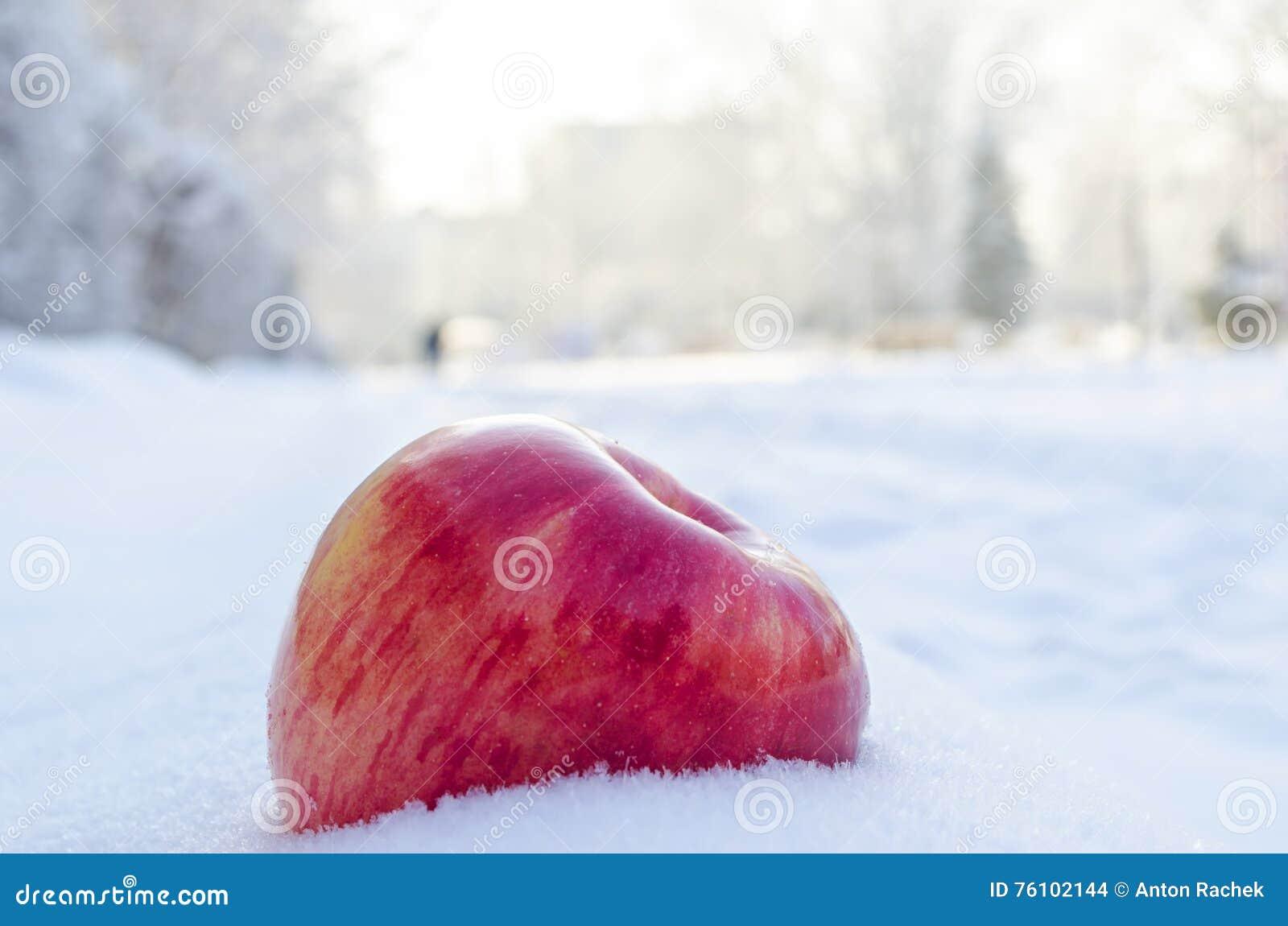 Красное яблоко на белизне и снеге воздуха