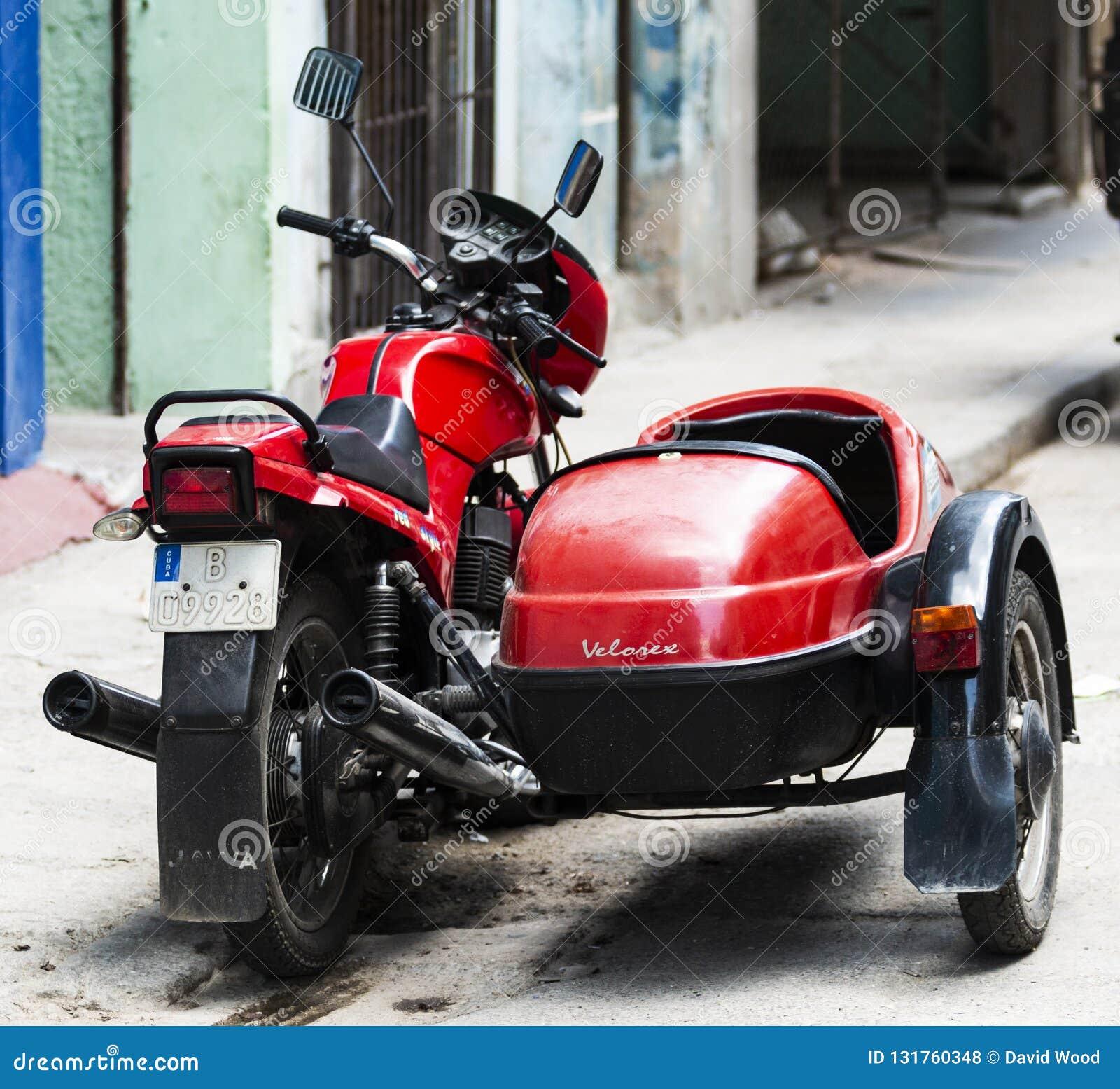 Красное mortocylcle Velorex с бортовым автомобилем припарковано на улице в Гаване Кубе