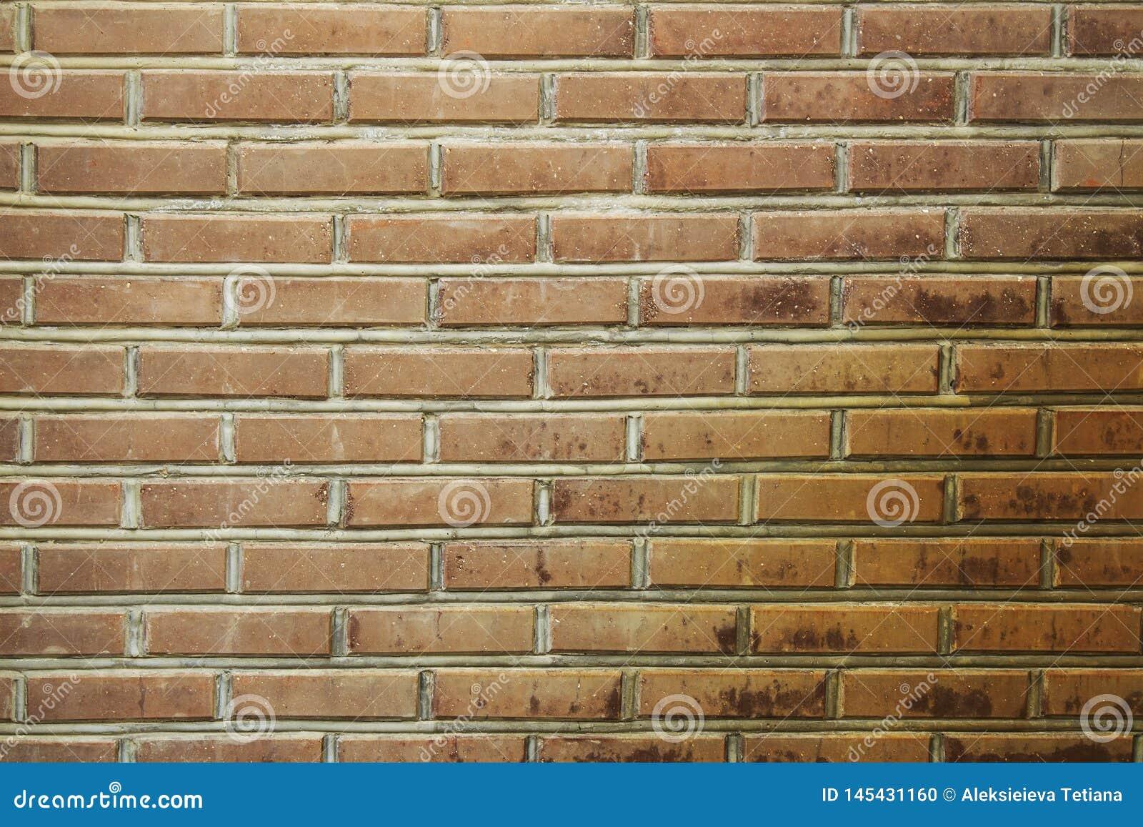 Красной, коричневой предпосылка текстурированная кирпичной стеной