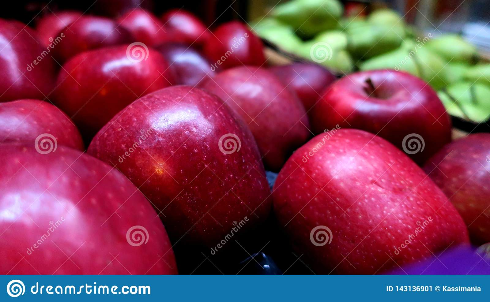 Красные большие свежие яблоки жмут