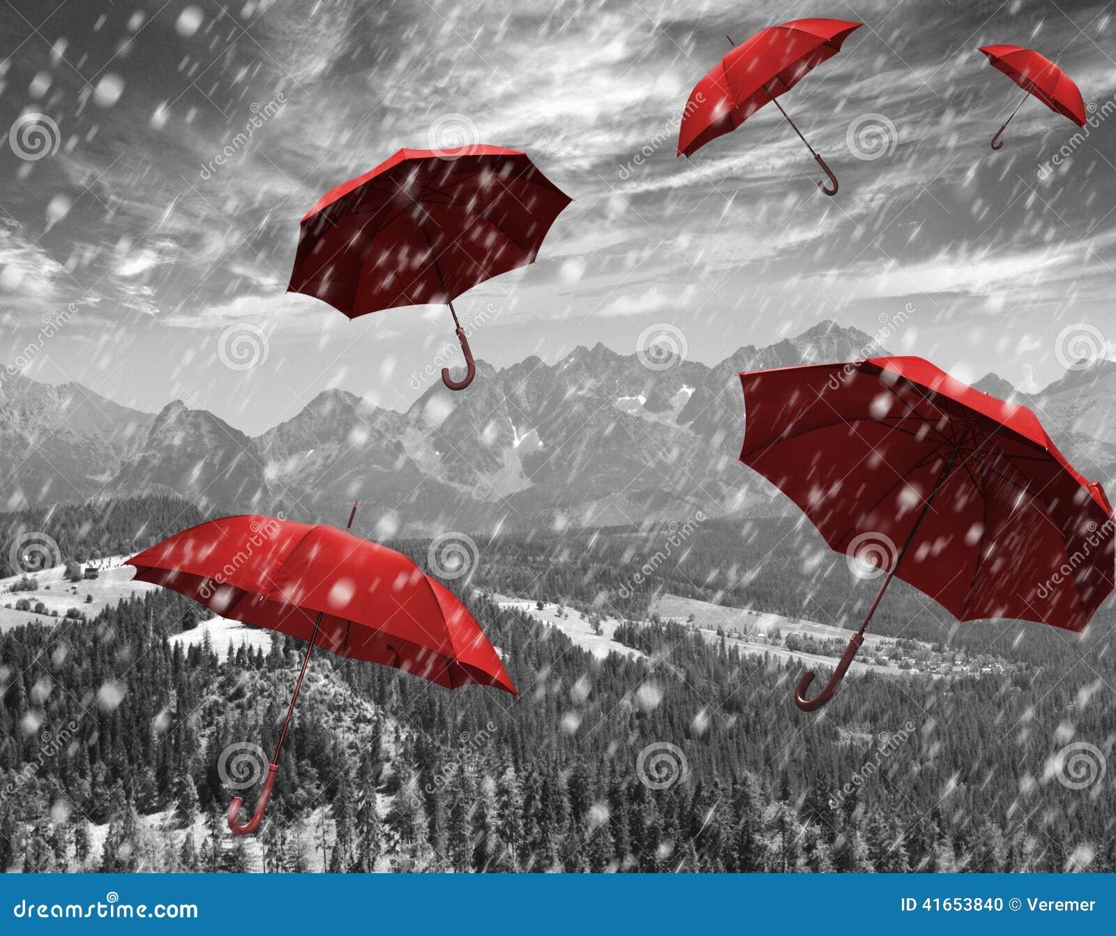 Красные зонтики летая в горах во время шторма