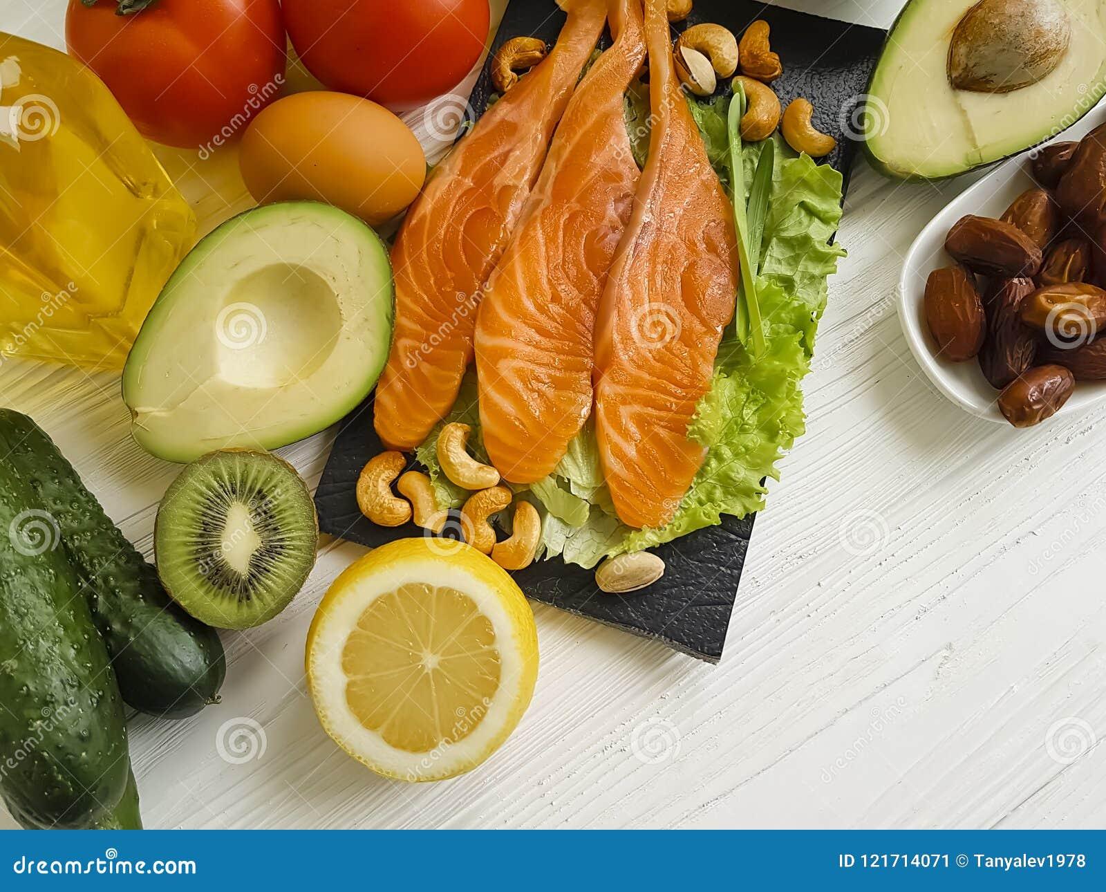 Красные рыбы, авокадо, чокнутый противоокислительн ингридиент протеина лимона на деревянной предпосылке