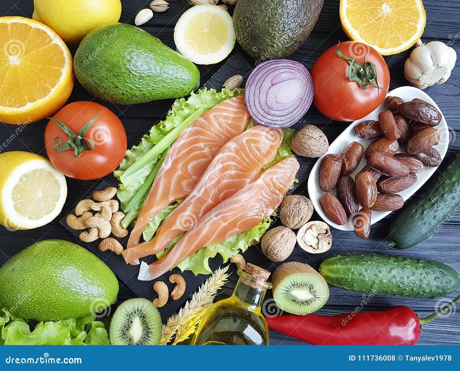 Красные рыбы, огурец обедающего выбора авокадоа чокнутый на черной деревянной, здоровой еде