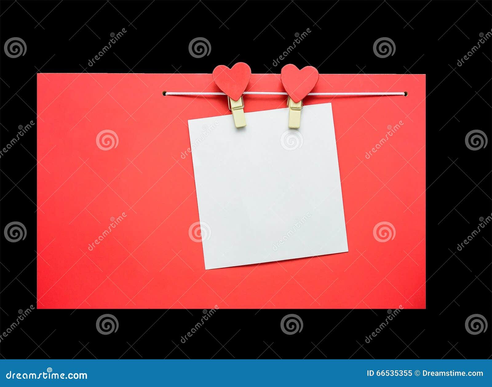 Красные сердца при зажимки для белья вися на веревке для белья изолированной на черной предпосылке