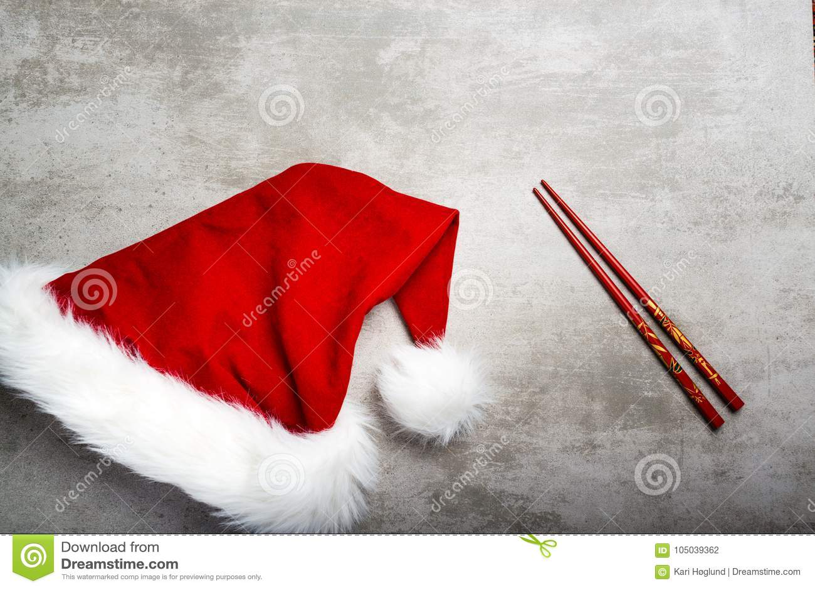 Красные шляпа и палочки santa на серой конкретной таблице