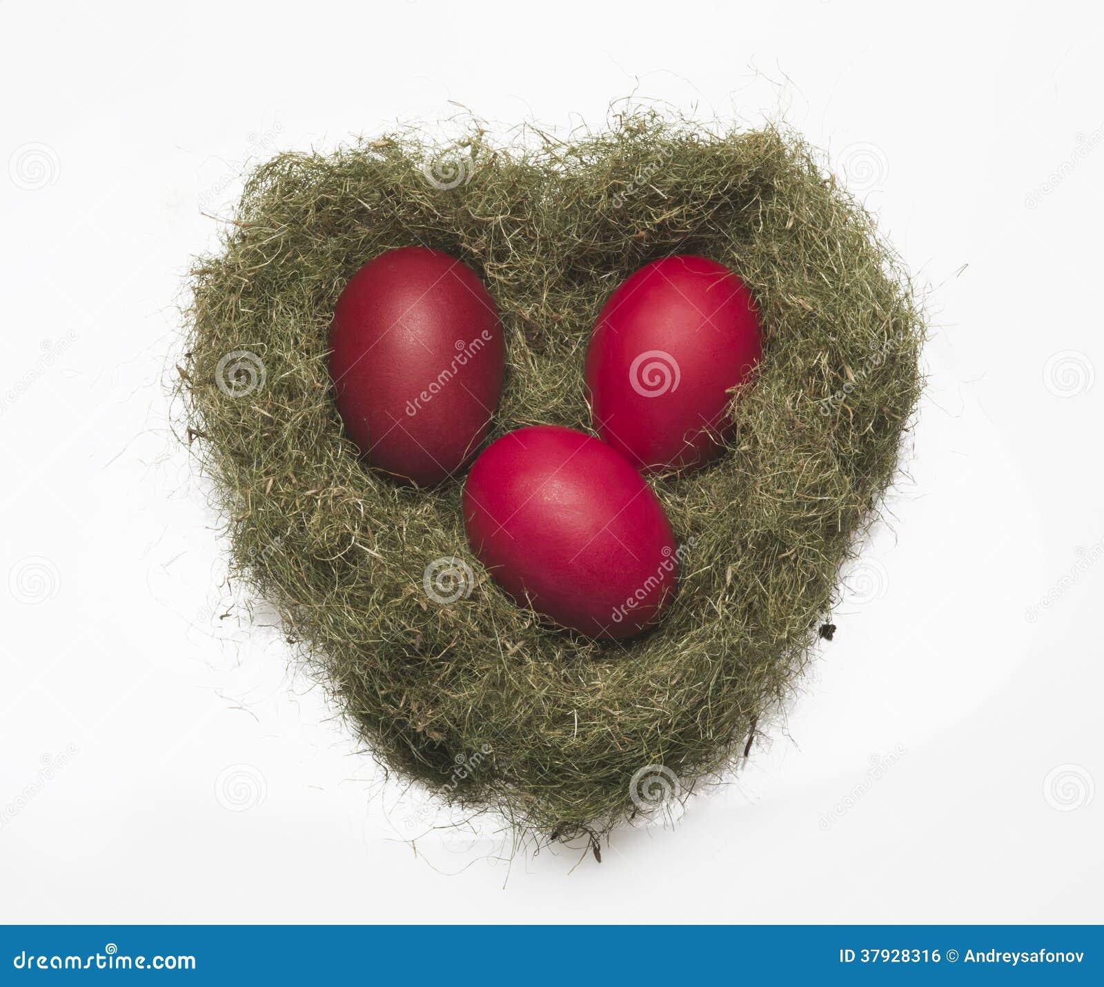 Красные яичка в гнезде на белой предпосылке