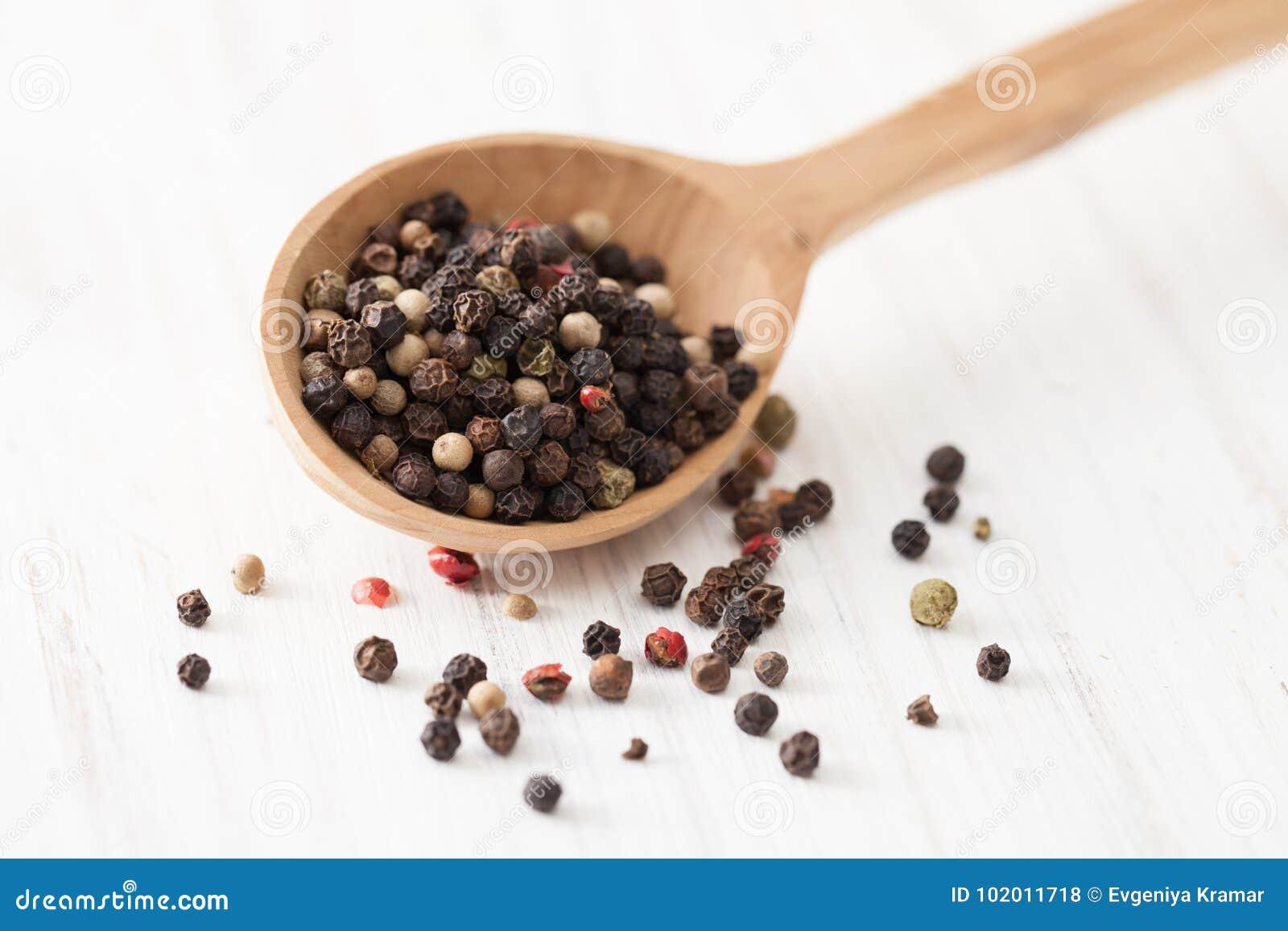 Красный, белый и черный перец в деревянной ложке на белом деревянном столе