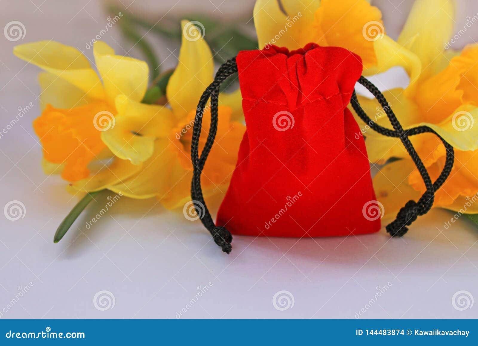 Красный мешок бархата с желтыми цветками на белой изолированной предпосылке