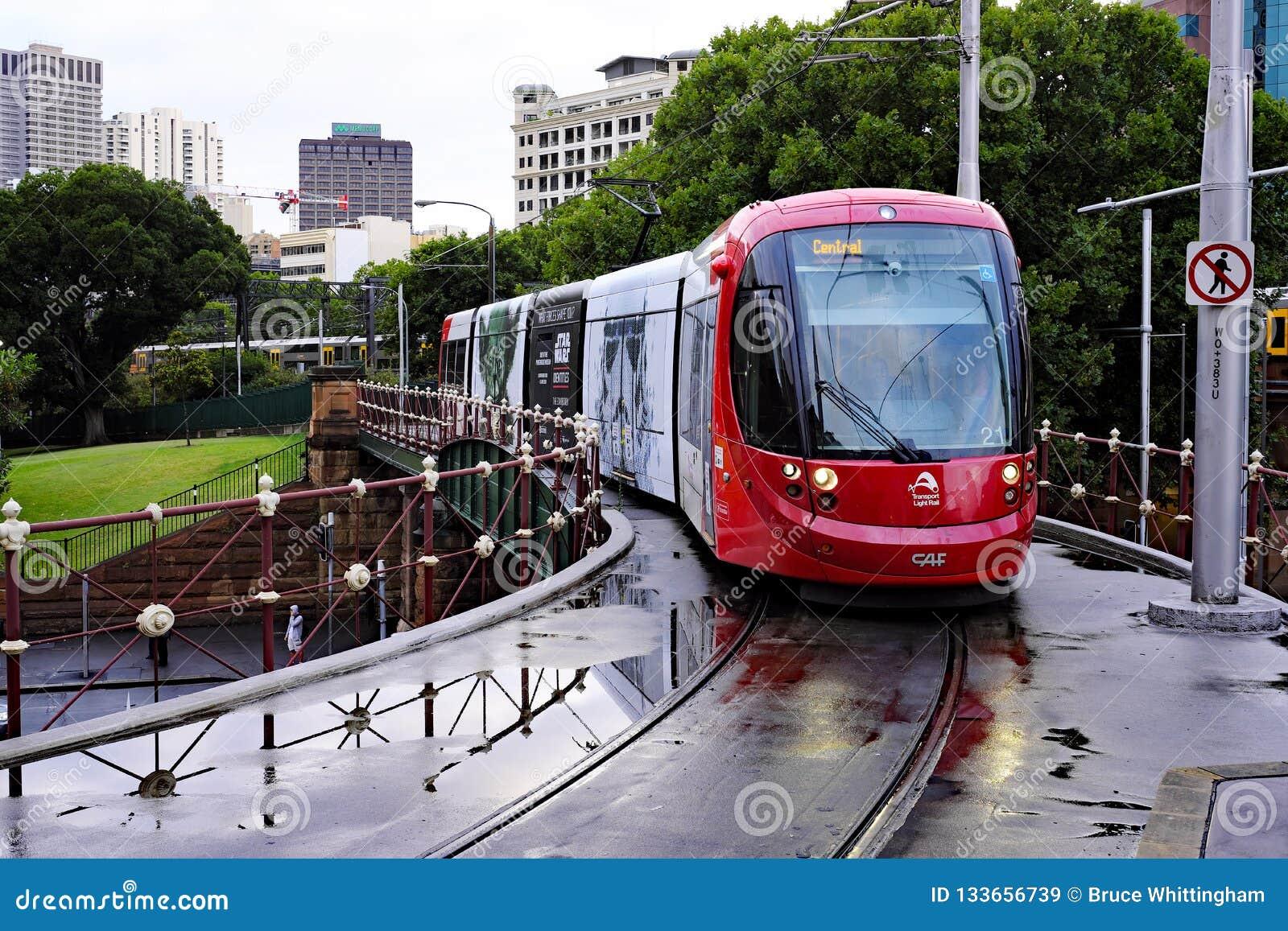 Красный поезд рельса света Сиднея причаливая центральному железнодорожному вокзалу, Австралии
