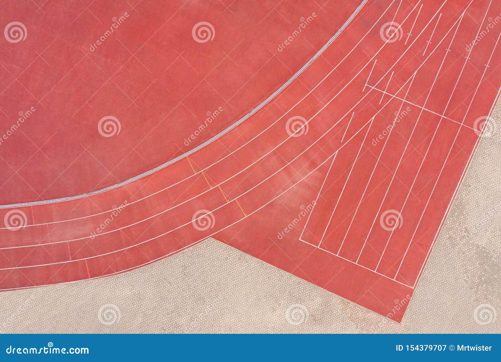 Красный синтетический резиновый атлетический идущий след на стадионе r