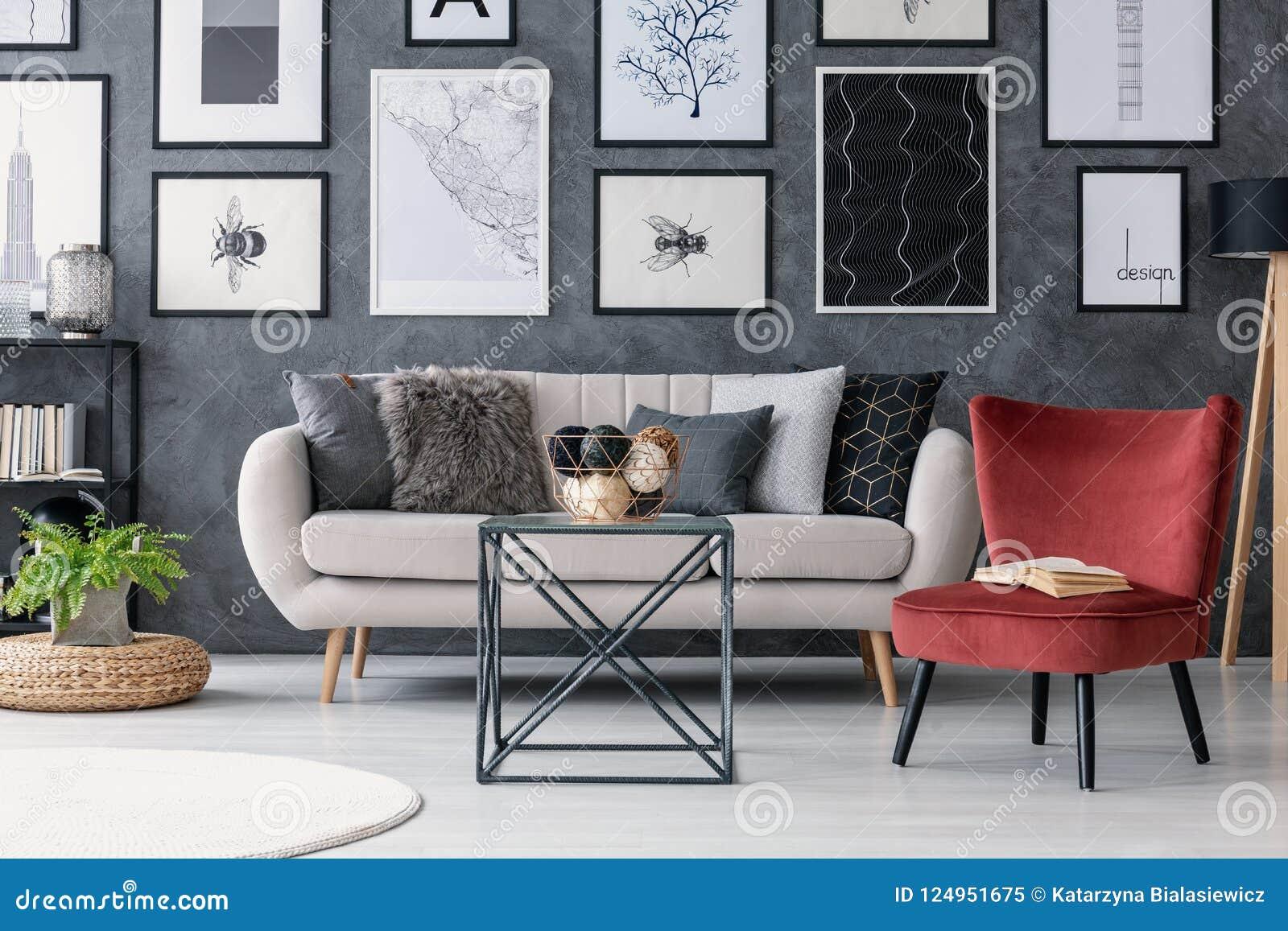 Красный стул рядом с таблицей и креслом в современном интерьере квартиры с галереей и заводом на pouf Реальное фото