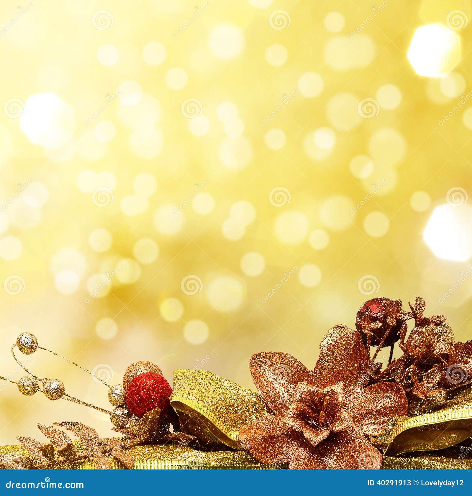 Красный цвет и безделушки рождества золота на предпосылке