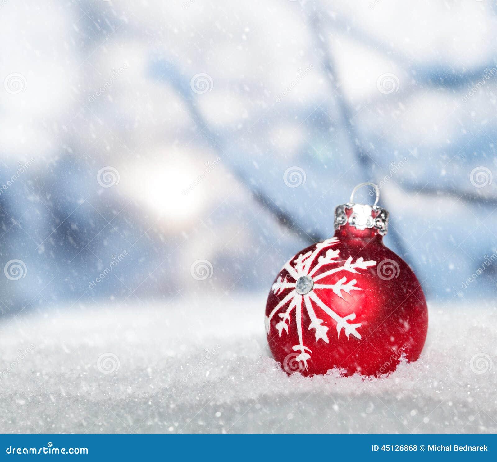 Красный шарик рождества на снеге против идя снег ландшафта зимы