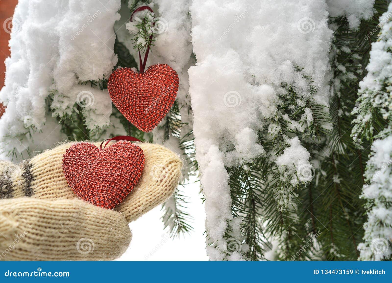 2 красных сердца и руки ткани на тяжелой снежной предпосылке ветви ели, около дома красного кирпича Веселое рождество, С Новым Го