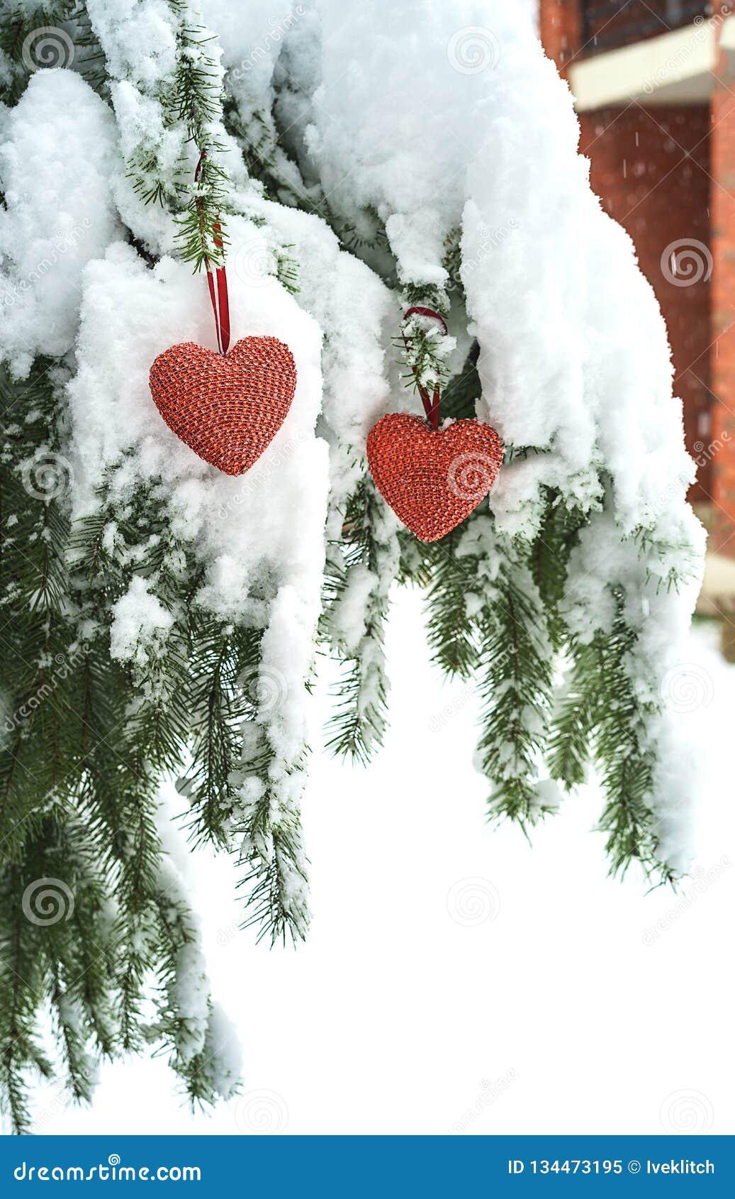 2 красных сердца ткани вися на тяжелой снежной ветви ели, около дома красного кирпича Веселое рождество, С Новым Годом! и Валента