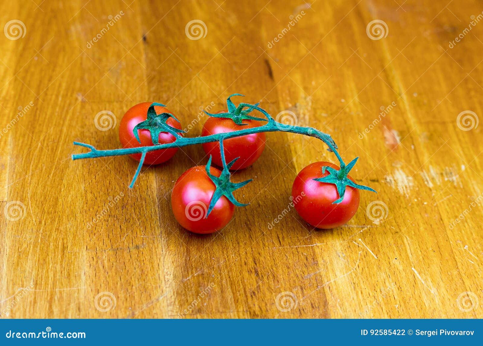 4 красных томата вишни на ветви на деревянном