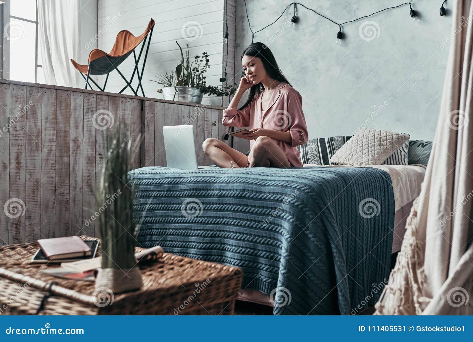 Красота занимаясь серфингом сеть Привлекательная молодая женщина используя компьютер