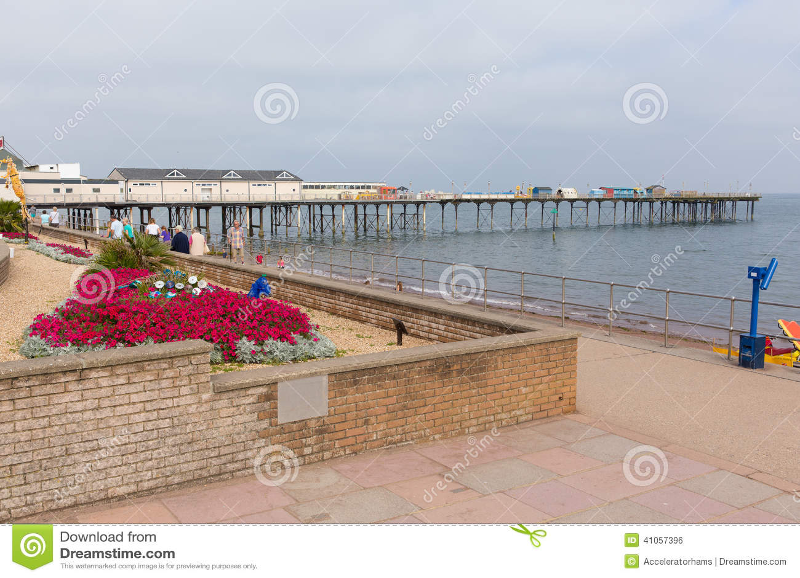 Красочная пристань Teignmouth цветков и отдыхающих и пляж Девон Англия Великобритания