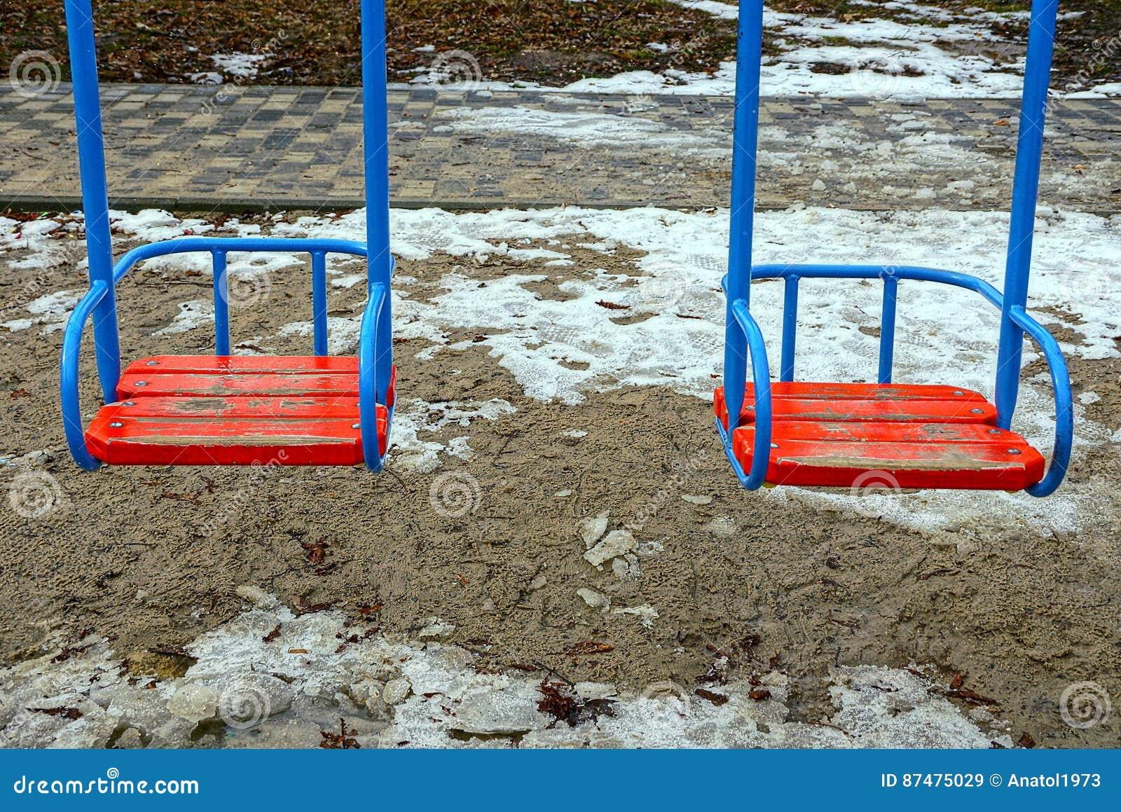 Красочное место качания ` s детей на спортивной площадке зимы