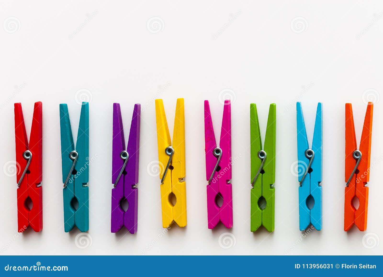 Красочные деревянные зажимки для белья на белой предпосылке с экземпляром размечают/концепцией разнообразия