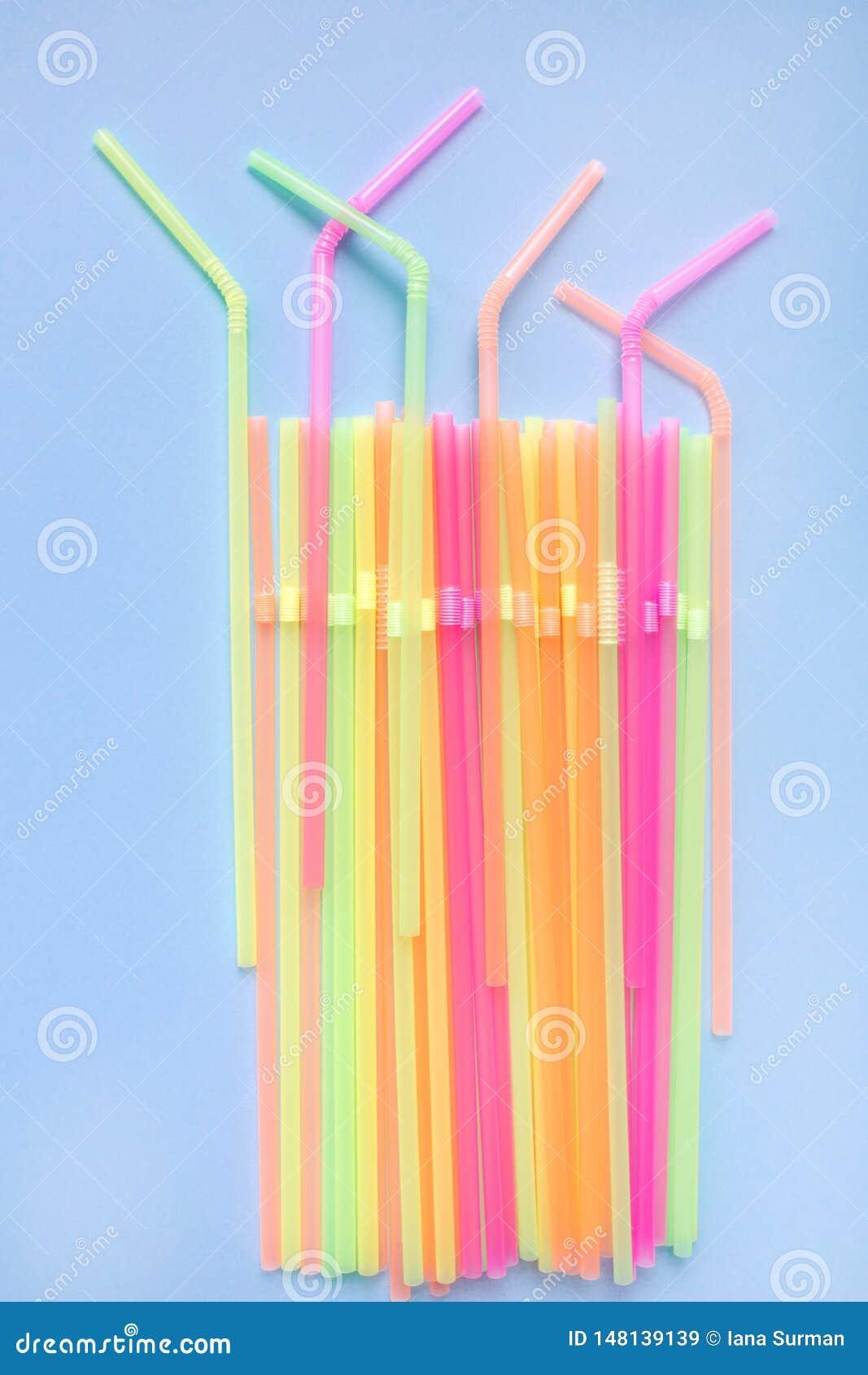 Красочные пластиковые соломы на голубой предпосылке Трубки коктейля
