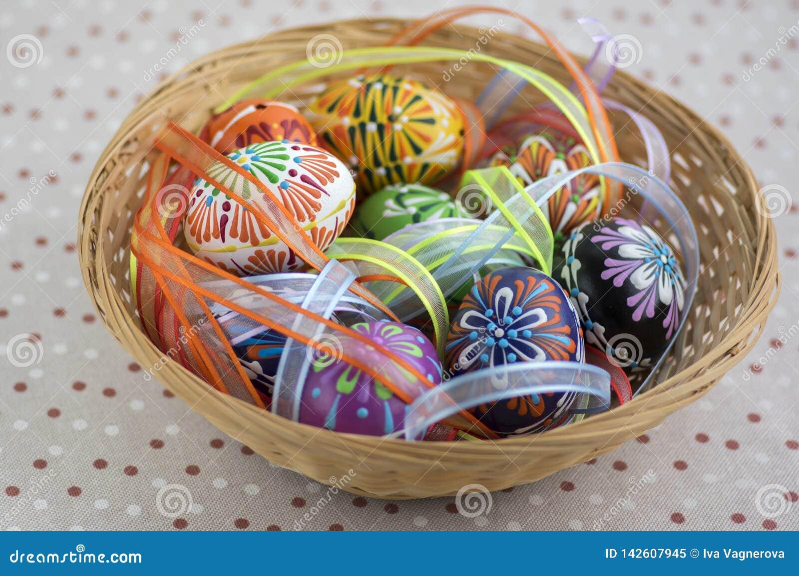 Красочные покрашенные пасхальные яйца в коричневой плетеной корзине покрытой с красочными лентами, традиционном натюрморте пасхи