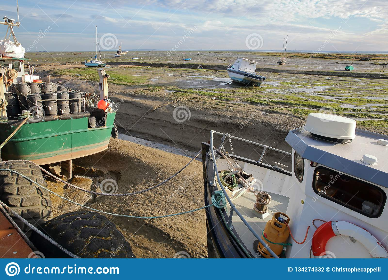 Красочные удя траулеры причаленные на набережной с грязным пляжем во время отлива на заднем плане, Leigh на море