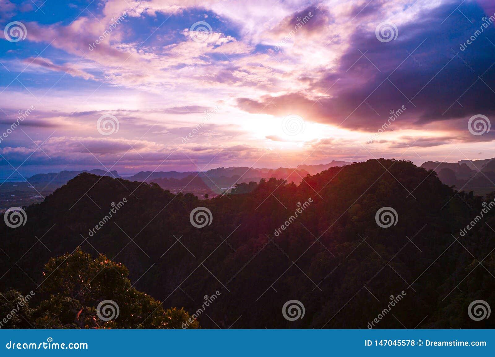 Красочный заход солнца с красивым видом от горы пещеры тигра над горами Krabi, Таиланда