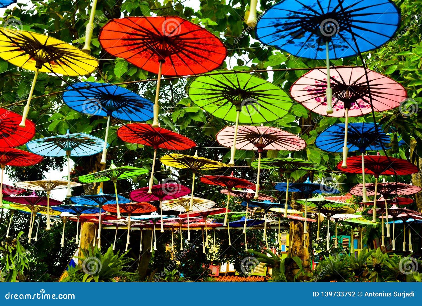Красочный зонтик бумаги радуги вися в небе