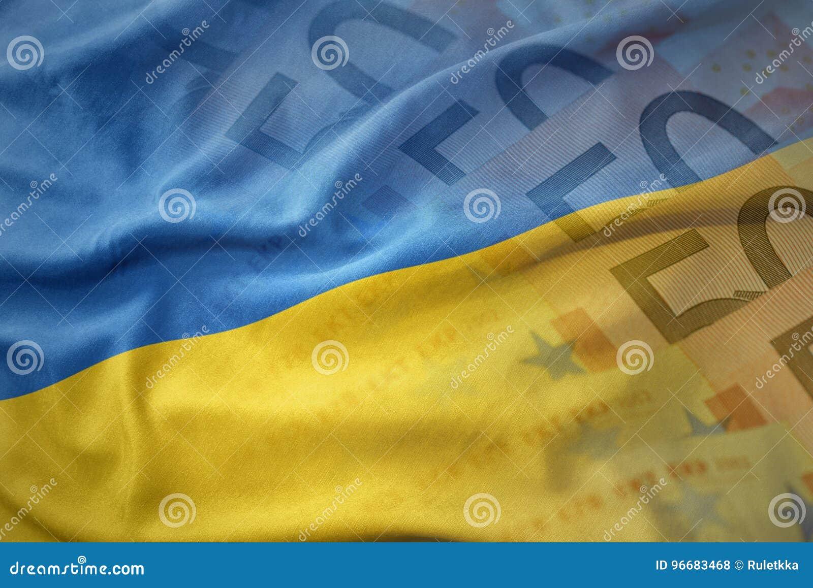 красочный развевая национальный флаг Украины на предпосылке банкнот денег евро