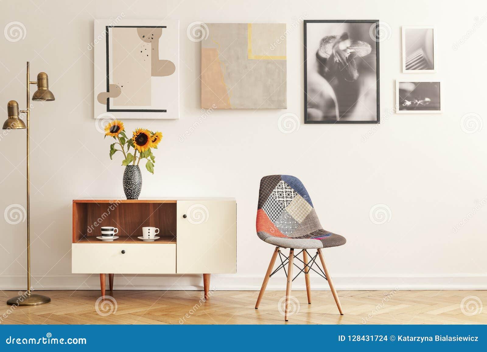 Красочный стул стоя в белом интерьере живущей комнаты с галереей на стене, кухонном шкафе с цветками и чашках чая