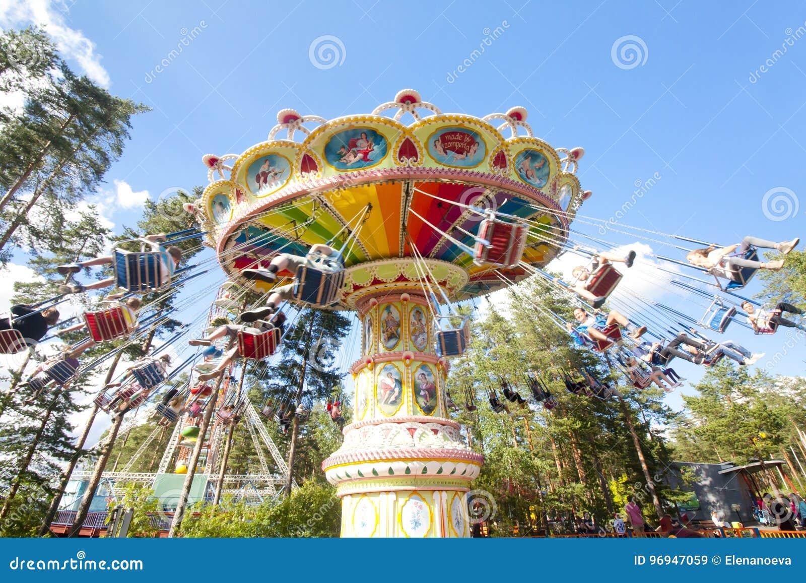 Красочный цепной carousel качания в движении на парке атракционов на предпосылке голубого неба