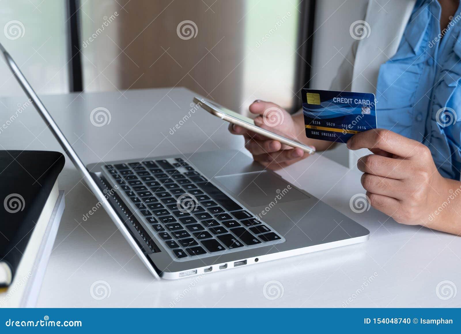Кредитная карточка пользы потребителя бизнес-леди для онлайн покупок по ее ноутбуку и телефону и сделать оплату приобретения в Ин