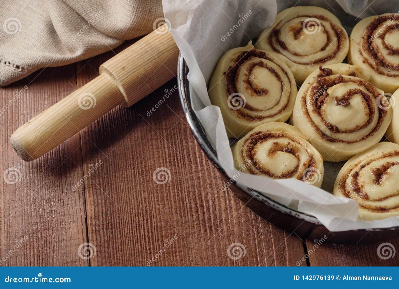 крены циннамона Свеже испеченные плюшки циннамона при специи и какао заполняя на пергаментной бумаге Взгляд сверху Сладостное дом
