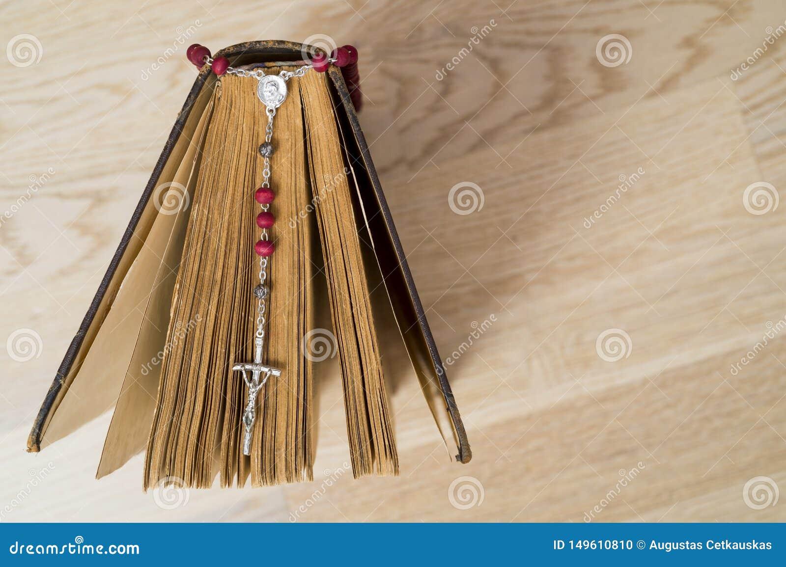 Крест на библии на деревянной предпосылке Святая книга